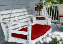 White Porch Swing With Red Cus...