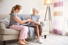 Caregiver Giving Glass Of Water To Senior Woman At Home