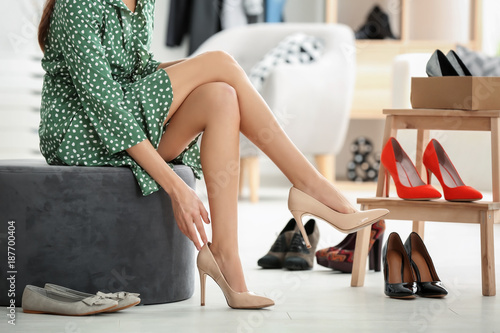 Young woman trying on shoes in shop