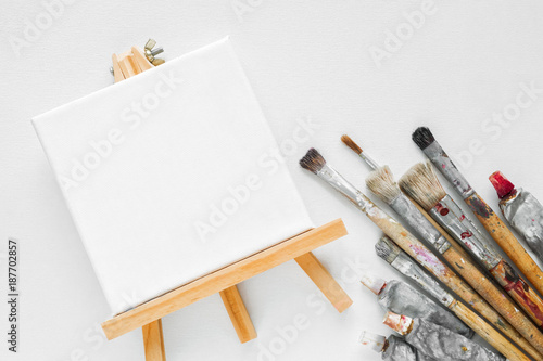 Canvas on easel, paint tubes and bundle of brushes for painting on white canvas background. Top view. Flat lay.