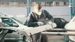 Man worker in automobile service - manual labor - polishes car, close up