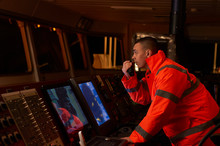 Pilot / Navigator On The Bridge During Night Hours Doing His Day-to-day Job With Binoculars And Radio