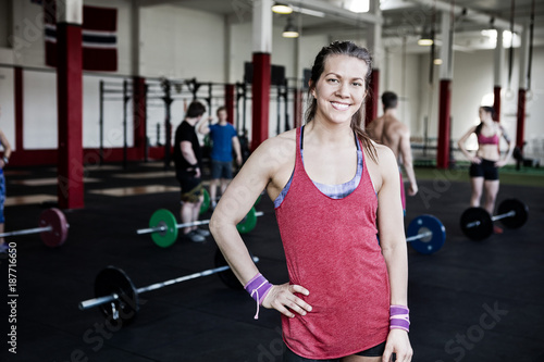a8254c3f7fc Fit Woman With Hand On Hip Standing In Fitness Center. By Tyler Olson