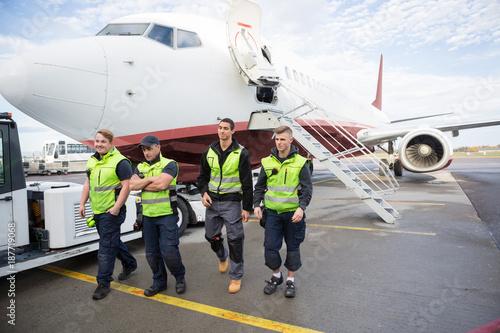 Foto  Confident Ground Crew Walking Against Airplane