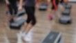 Young healthy sportive women training at gym using step boards. Out of focus video footage.