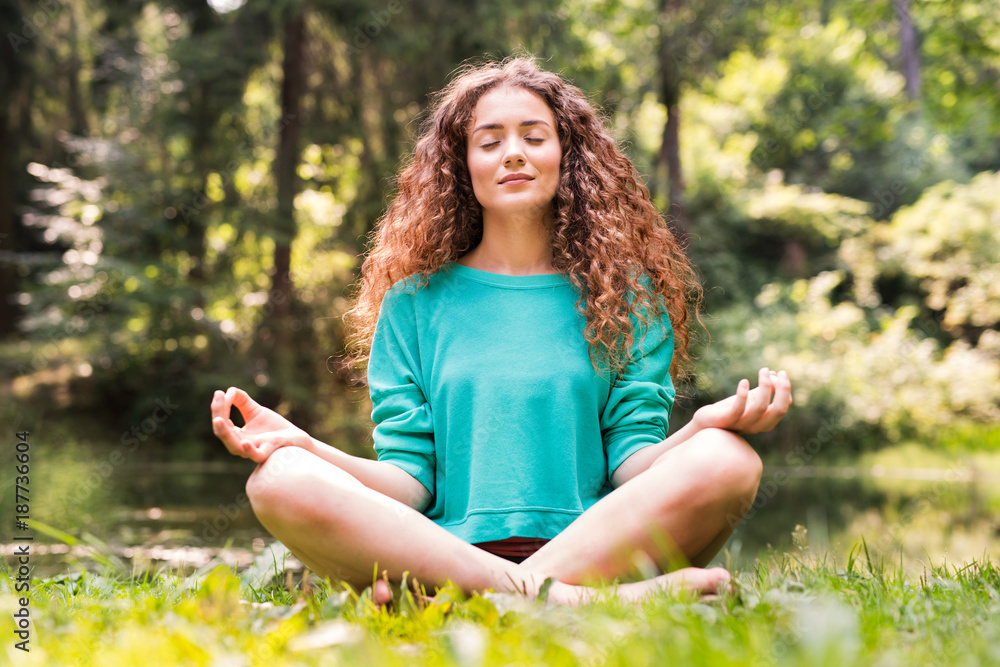 Fototapeta Beautiful girl practices yoga in the morning forest.