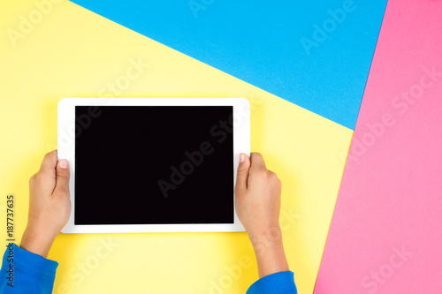 Kid hands with tablet computer on colorful background