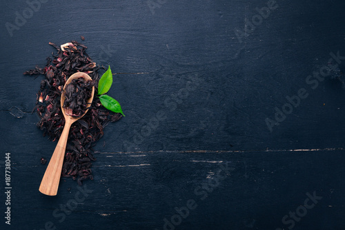 Staande foto Thee Dry Hibiscus tea. On a wooden background. Top view. Copy space.