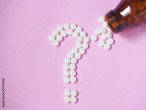 Fotografia  Question mark made by white pills spilling out of brown glass bottle on pink background