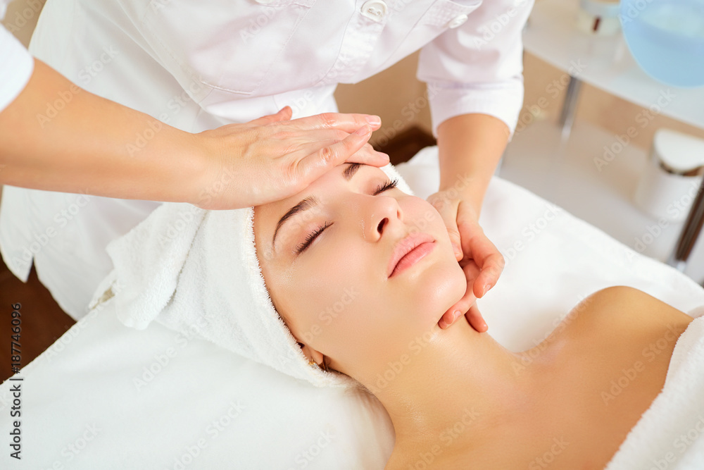 Fototapeta Beautiful woman at a facial massage at a spa salon.