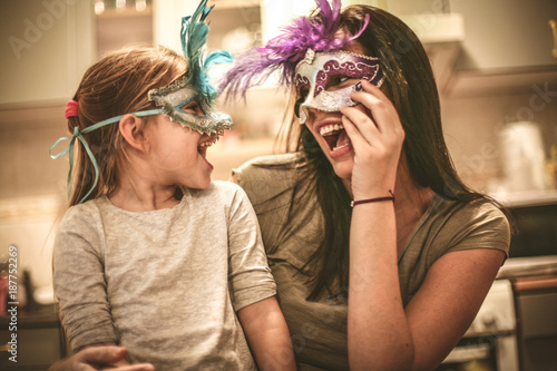 Foto Mother and daughter have play with carnival mask.