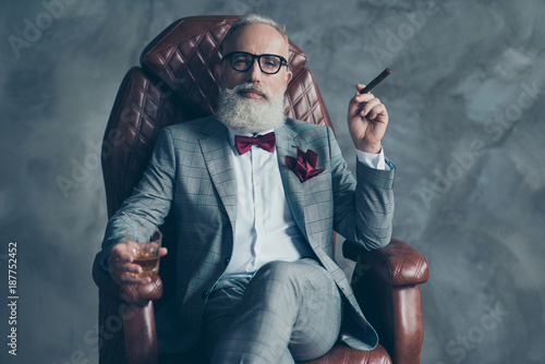 Cool man in glasses, hold cigarette, glass with brandy, in formal wear, tux with red bowtie and pocket square, sit in leather chair over gray background, looking to the camera, shares, stock, money