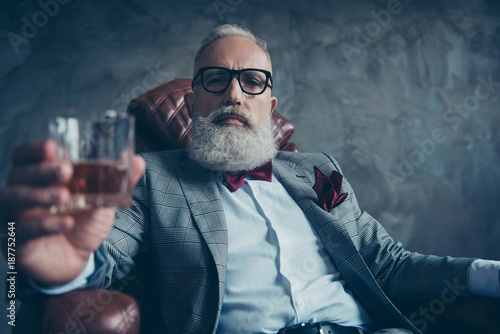 Fényképezés  Attractive, old investor in spectacles, hold glass with brandy, in tuxedo with r