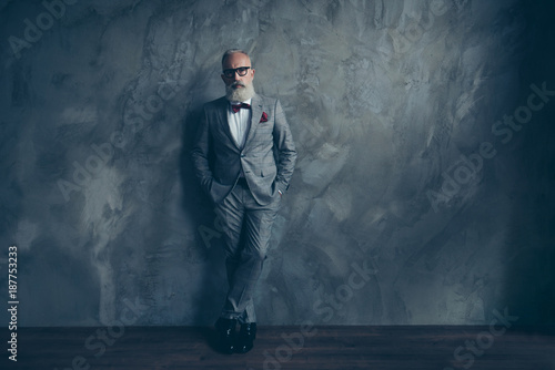Fototapety, obrazy: Full length portrait of stunning perfect brutal harsh old man in suit with bow-tie holding hands in pockets, leg by foot standing on wooden floor over gray wall