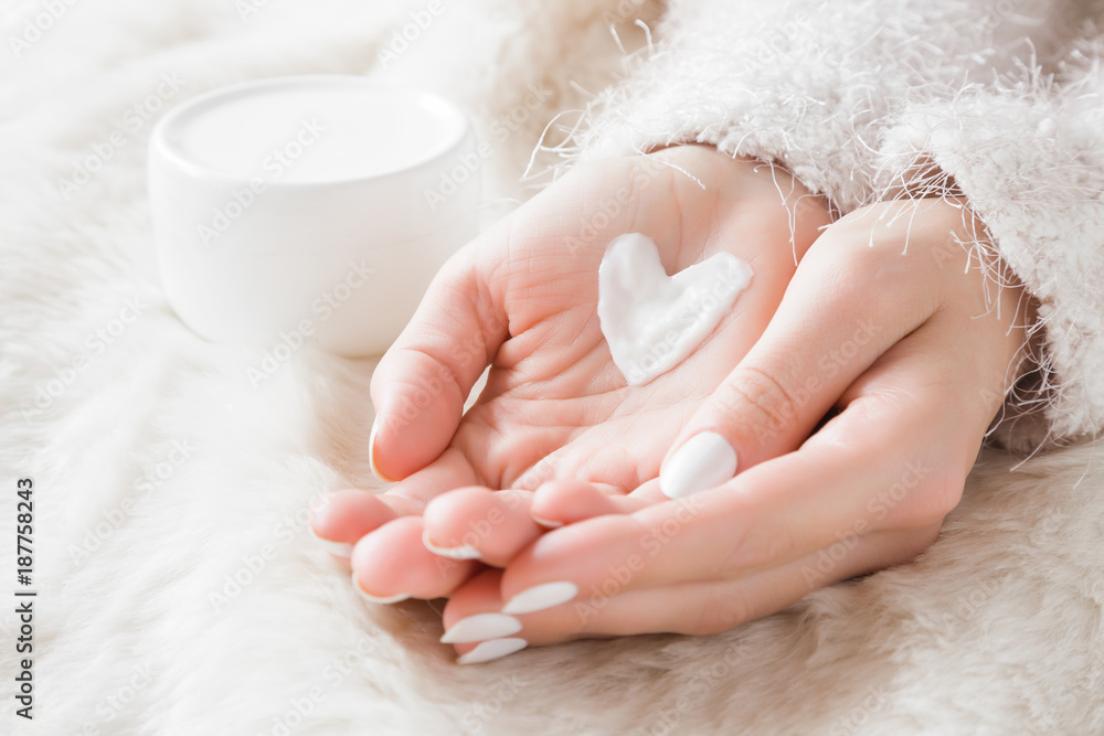 Fototapeta Beautiful groomed woman's hands with cream jar on the fluffy blanket. Moisturizing cream for clean and soft skin in winter time. Heart shape created from cream. Love a body. Healthcare concept.