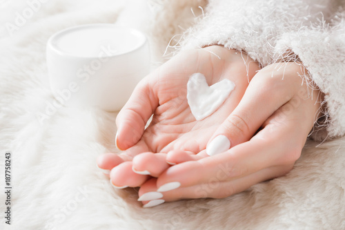 Fototapeta Beautiful groomed woman's hands with cream jar on the fluffy blanket