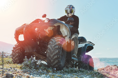 Fotografiet  A man is driving ATV on off-road. Sunny.