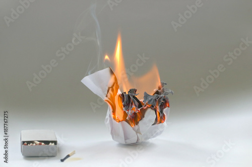 Crumpled paper burning in fire and matchbox Fototapet