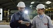 Two engineers in helmets with a tablet computer walking and discussing their project. Planning inside a big factory.