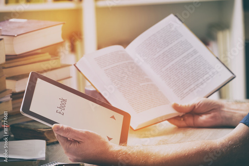 Man holding a modern ebook reader and book in library