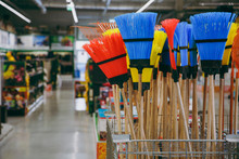Set Of Colorful Brooms For Cleaning And Sweeping In The House In A Big Store For Housewives.