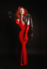 Red-haired Woman With Curly Hair In Red Dress And Long Gloves Smoke On Black Background. Girl Is Dressed In Retro Style With Natural Fur And The Mouthpiece With A Cigarette