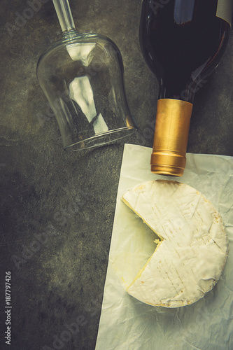 Soft French Camambert Cheese with Cut out Wedge on White Parchment Paper Empty Glass Wine Bottle on Dark Stone Background. Top View Flat Lay Copy Space Rustic Style