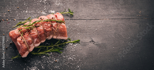 Valokuva  Raw meat Beef fillet with rosemary and spices on a black wooden background