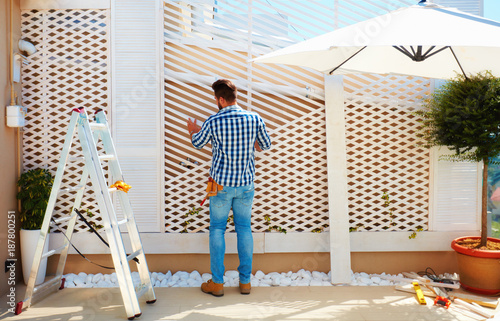 Fotografie, Obraz  young adult man building wooden pergola wall on rooftop patio zone