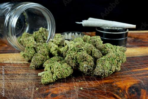 Vászonkép One ounce marijuana with jar, joints and grinder against black background