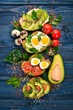 A set of avocado sandwiches, cherry tomatoes and quail eggs and chia seeds. On a wooden background. Top view. Free space for your text.