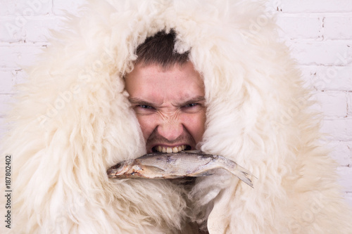 Photo  a man in a white skin with a fish in his mouth expresses anger