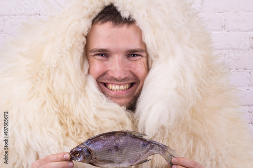 Photo man in white skin smiling holding a fish in hands