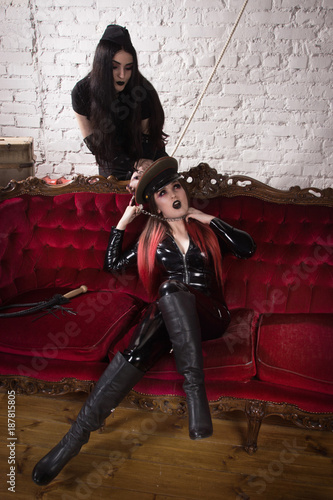 The woman in uniform strangles the second woman with a chain from the handcuffs Canvas Print