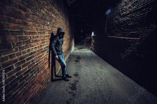Photo Suspicious man in dark alley waiting for something