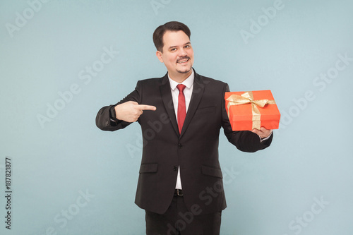Fotografie, Obraz  Happy man in black suit holding and pointing red gift box