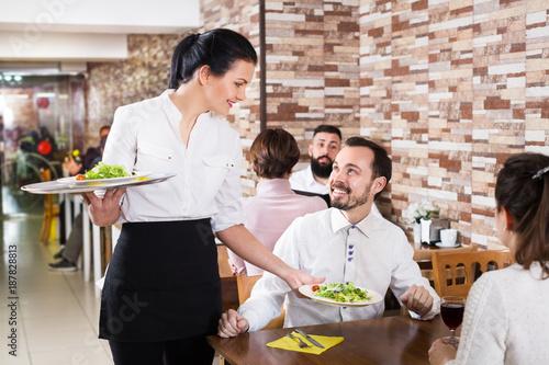 Leinwand Poster Waitress taking table order at tavern