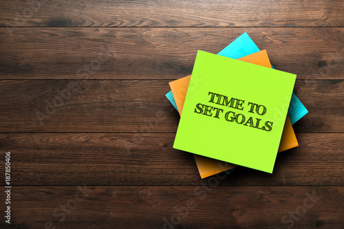 Photo  Time To Set Goals, the phrase is written on multi-colored stickers, on a brown wooden background