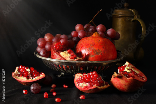 Still life with pomegranates, grapes and brass pitcher