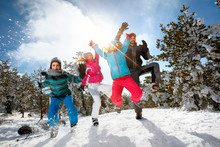 Family With Children High Jump On Winter Day On Ski Vacation And Having Fun