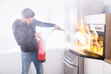 Man Using Fire Extinguisher To Stop Fire Coming From Oven