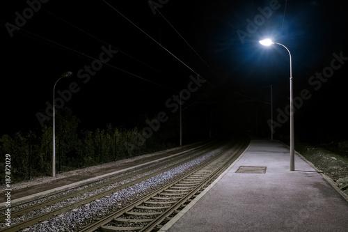 Türaufkleber Eisenbahnschienen Ruhiger einsamer verlassener Bahnsteig bei Nacht mit Laternenlicht