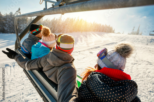 skiers and snowboarders on ski lift in the mountain at winter vacations