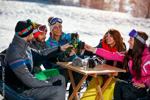 happy friends cheering with drink after skiing day in cafe at ski resort