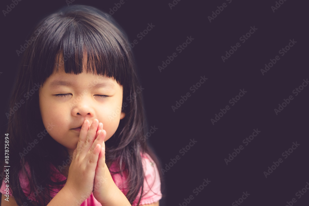 Fototapeta Little girl praying in the morning.Little asian girl hand praying,Hands folded in prayer concept for faith,spirituality and religion.Black background.