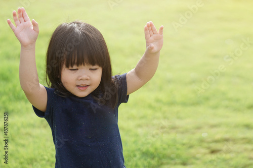 Photographie Little girl praying and raise hands in the morning for faith, spirituality and religion