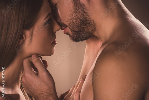 Foto sensual couple kissing and looking at each other, on brown