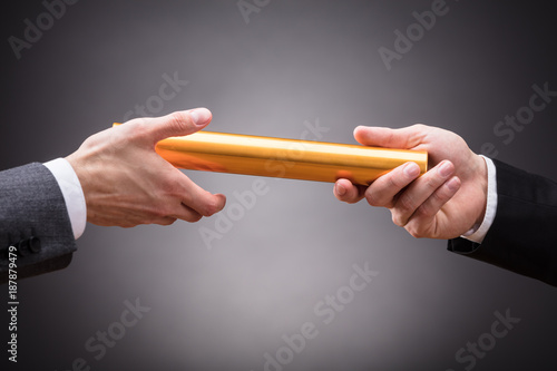 Fotografia  Person Passing Baton To Businessperson