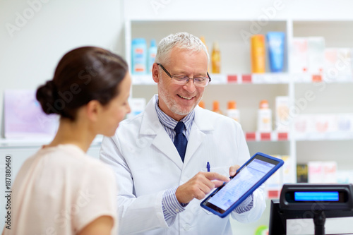 In de dag Apotheek apothecary and customer with tablet pc at pharmacy
