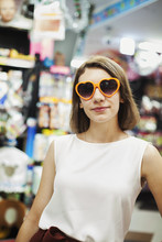Young Woman With Brown Hair Wearing White Sleeveless Top Wearing Orange Heart Shaped Sunglasses, Looking At Camera.